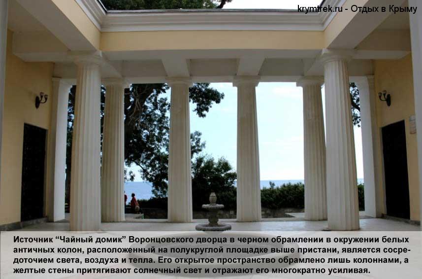 """Источник """"Чайный домик"""" Воронцовского дворца в черном обрамлении в окружении белых античных колон, расположенный на полукруглой площадке выше пристани, является сосредоточием света, воздуха и тепла. Его открытое пространство обрамлено лишь колоннами, а желтые стены притягивают солнечный свет и отражают его многократно усиливая."""